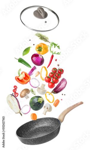 Fototapeta Frying pan and flying vegetables on white background obraz