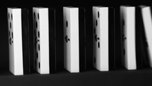 Domino Effect. Row Of White And Black Dominoes Falling Down. Chain Reaction. The Domino Principle. Falling Dominoes. Board Game. Lateral Shot.
