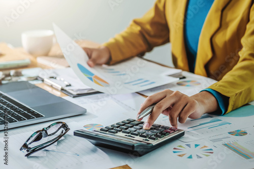 .Business woman working in finance and accounting Analyze financial budget in th Wallpaper Mural