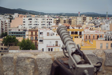 View From Ibiza Town Eivissa  From The Town Fort Castle With An Old Medieval Protection Canon  In Foreground Old White And Yellow Mediterranean Buildings Top View Of City