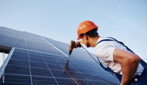 Obraz Using cordless screwdriver. Male worker in blue uniform outdoors with solar batteries at sunny day - fototapety do salonu