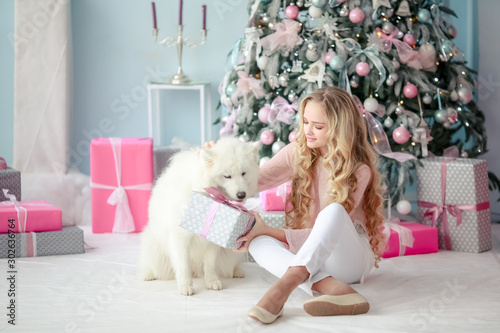 Fotografía  A girl sits with her dog surrounded by New Year's gifts under a Christmas tree in a photo studio