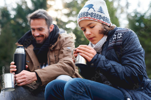Teenage boy drinking hot tea in autumn forest