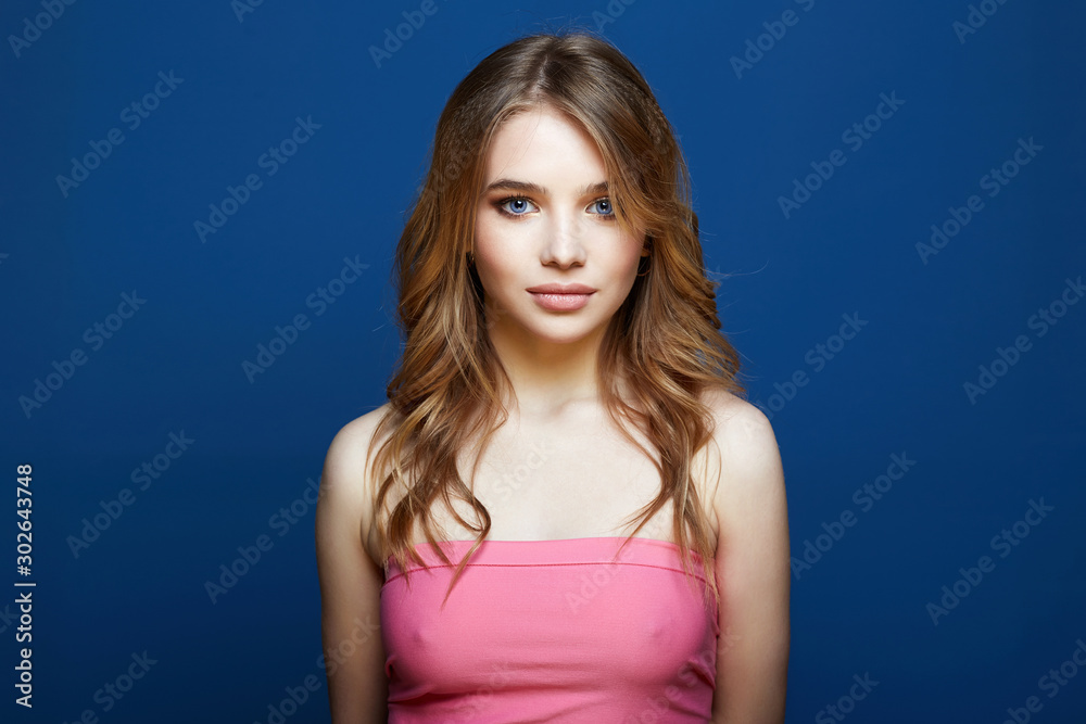 Fototapeta Beautiful young woman in pink dress over blue background