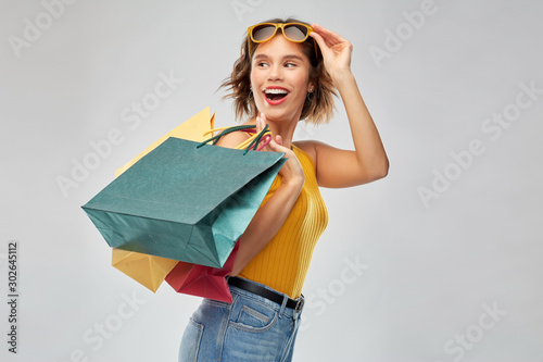 Fotomural  sale and people concept - happy smiling young woman in mustard yellow top and je