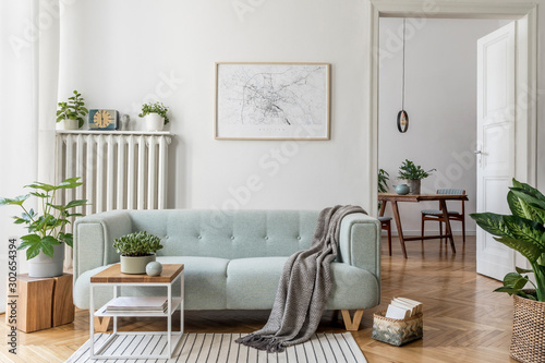 Fototapeta Stylish scandinavian living room with design mint sofa, furnitures, mock up poster map, plants and elegant personal accessories. Modern home decor. Open space with dining room. Template Ready to use.  obraz na płótnie