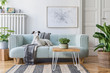 Leinwanddruck Bild - Stylish scandinavian living room interior of modern apartment with mint sofa, design coffee table, furnitures, plants and elegant accessories.  Beautiful dog lying on the couch. Home decor. Template.