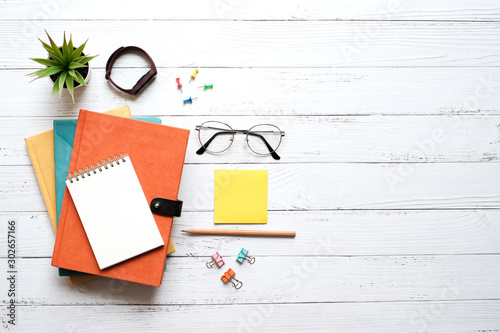 Fototapeta Flat lay education and black to school concept on white wooden table desk with blank notepad and stack of book , green plant and supplies, Top view with copy space, work space obraz