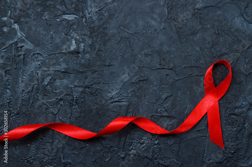 Photo Red ribbon as symbol of aids awareness on black background