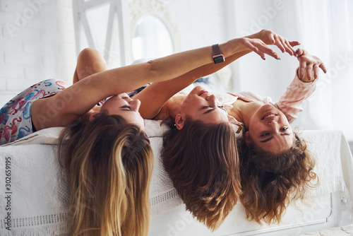 Fototapeta Lying on the bed with hair hangs down. Happy female friends having good time at pajama party in the bedroom obraz