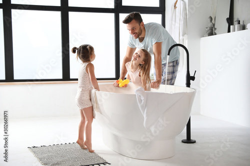 Obraz Young father with little daughters in bathroom - fototapety do salonu