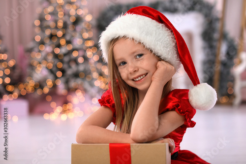 Cute little child with Christmas gift at home