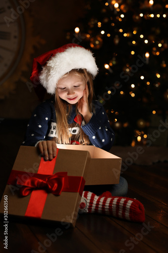 Cute child opening magic gift box near Christmas tree at night