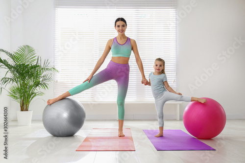 Fototapeta Woman and daughter doing exercise with fitness balls at home obraz