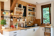 Interior Of Cozy Wooden Kitchen With Window In A Cottage In The Country.  Vintage Kitchenware And Rustic Decor With Sink And Kitchen Shelves. Light Indoors.