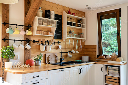 Leinwand Poster  Interior of cozy wooden kitchen with window in a cottage in the country