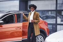 Young African American Woman In Glasses Stands Outdoors Near Modern Car