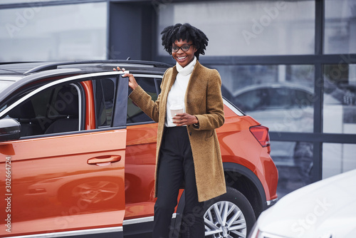 Photo Young african american woman in glasses stands outdoors near modern car