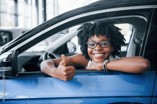 Obraz Shows thumb up. Young african american woman sits inside of new modern car - fototapety do salonu