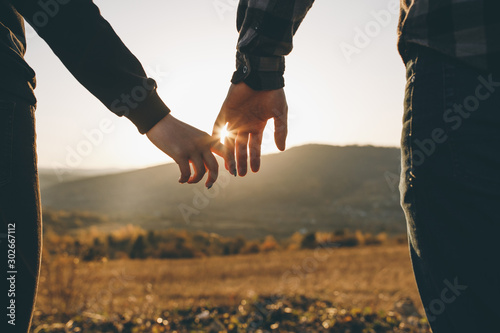 Obraz Close-up of hands joining together with sunlight flare in the background. Beautiful romantic moment between two lovers - fototapety do salonu