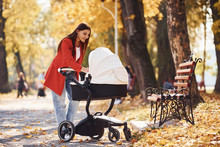 Mother In Red Coat Have A Walk With Her Kid In The Pram In The Park At Autumn Time