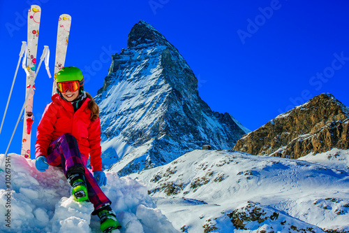 Foto auf AluDibond Dunkelblau Portrait of happy young girl in the snow, ski slope and Matterhorn in the background.