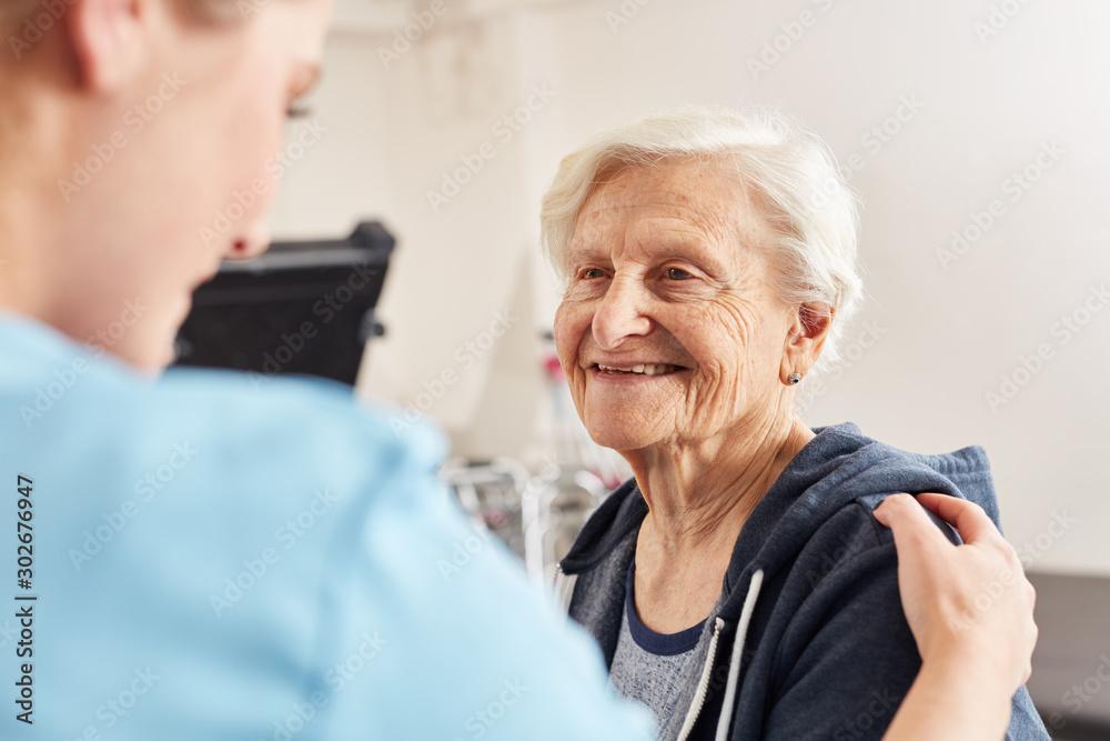 Fototapeta Therapeutin motiviert Seniorin als Patient