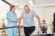 Physiotherapeutin hilft Senior auf dem Laufband