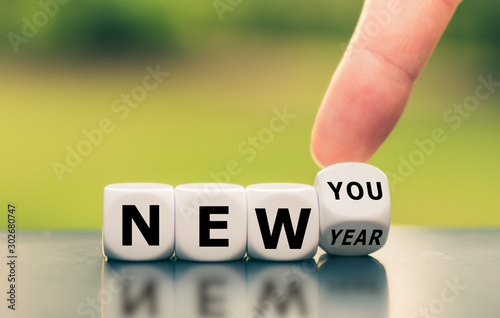 Fotografia  Hand turns a dice and changes the expression new year to new you