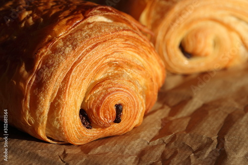 Photo Freshly backed french pastry - petit pain au chocolat shiny in the rays of the m