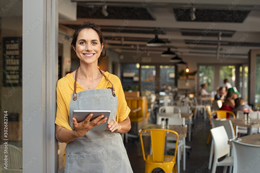 Fototapeta Small business owner at entrance looking at camera
