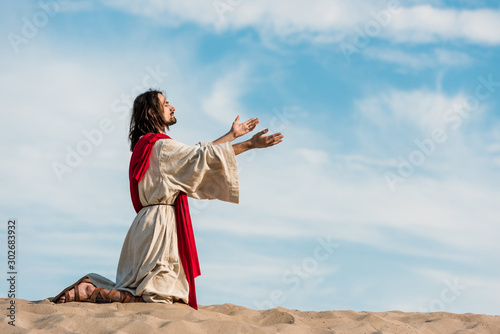 Fotografie, Obraz jesus praying on knees on sand in desert against sky