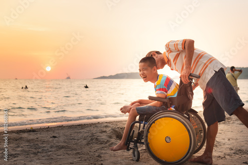 Obraz Asian special child on wheelchair is happily on the beach with father,Dad and son spend holiday to travel and learning about nature around the sea,Life in the education age,Happy disabled kid concept. - fototapety do salonu