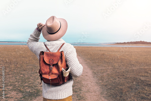 Obraz young man traveling through nature with backpack and hat - fototapety do salonu