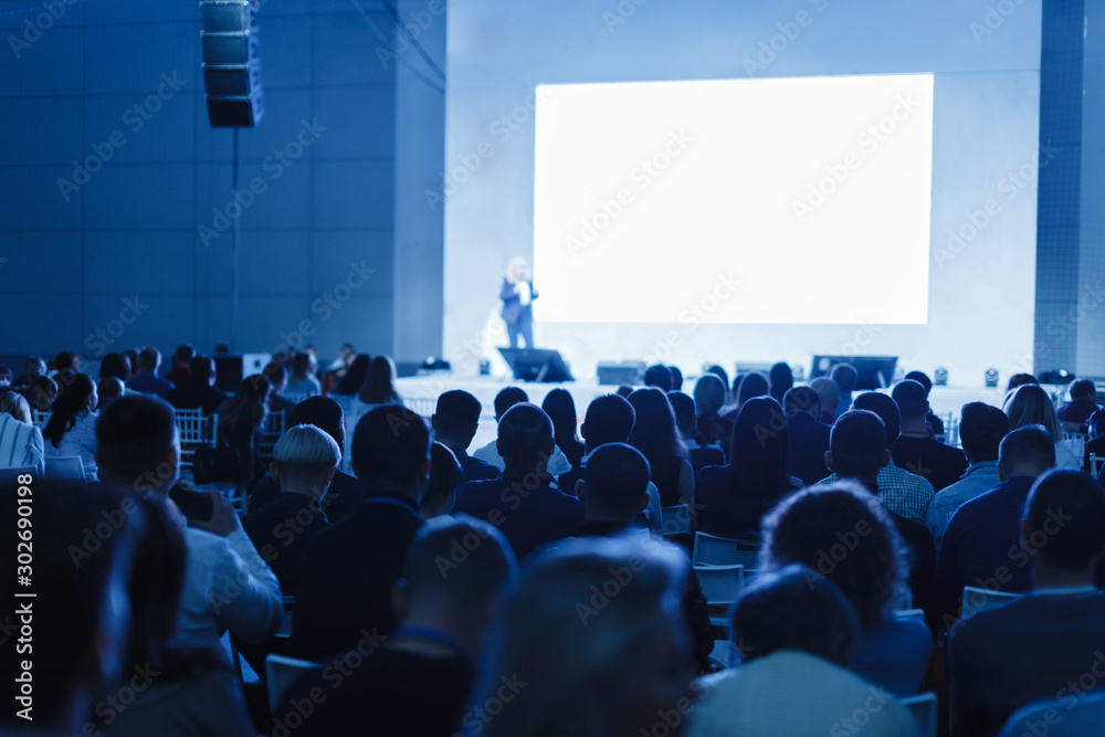 Fototapeta Business and Entrepreneurship concept. Speaker giving a talk in conference hall at business event. Audience at the conference hall. Focus on unrecognizable people