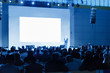 Speaker Giving a Talk at Business Meeting. Audience in the conference hall. blue tinted photo Focus on unrecognizable people