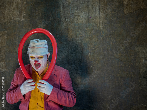 Photo Crazy aggressive clown with red ball and shadow