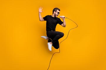 Fotografija profila cijelog tijela ludog hipstera koji skače visoko držeći mikrofon ljubitelj glazbe pjeva omiljenu pjesmu nosi sunčane naočale crne majice hlače izolirana žuta boja pozadine