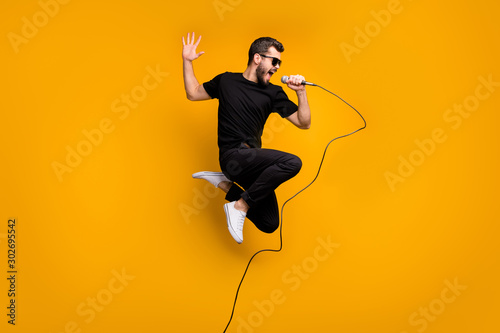 Full body profile photo of crazy hipster guy jumping high holding microphone music lover singing favorite song wear sun specs black t-shirt pants isolated yellow color background