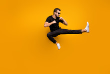 Full Length Photo Of Handsome Guy Jumping High Practicing Self Defense Kicking Confident Facial Expression Wear Sun Specs Black T-shirt Pants Isolated Yellow Color Background