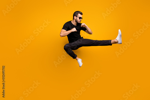 Valokuva Full length photo of handsome guy jumping high practicing self defense kicking c