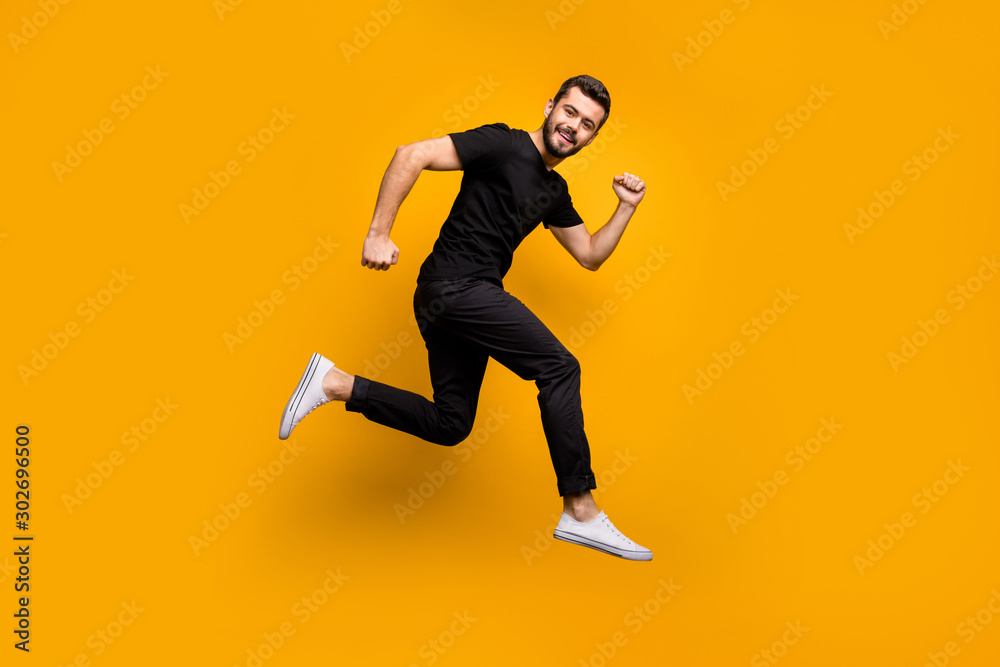 Fototapeta Full body profile photo of handsome millennial guy jumping high rushing shopping mall best black friday offers season wear black t-shirt trousers isolated yellow color background
