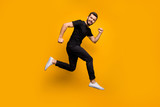 Full body profile photo of handsome millennial guy jumping high rushing shopping mall best black friday offers season wear black t-shirt trousers isolated yellow color background