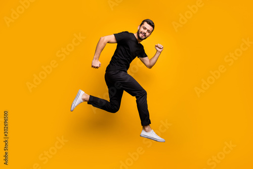Obraz Full body profile photo of handsome millennial guy jumping high rushing shopping mall best black friday offers season wear black t-shirt trousers isolated yellow color background - fototapety do salonu