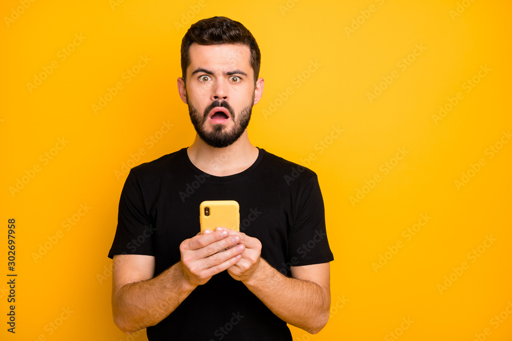 Fototapeta Portrait of impressed guy use his cellphone read unbelievable social network blogging information feel confused emotions stay stupor wear modern clothes isolated yellow color background