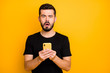 Leinwandbild Motiv Portrait of impressed guy use his cellphone read unbelievable social network blogging information feel confused emotions stay stupor wear modern clothes isolated yellow color background