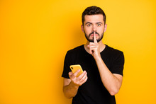 Censorship No Telling Secret Concept. Serious Guy Blogger Hold Use Cellphone Search Private Fake News Show Mute Quiet Sign Index Finger Wear Black T-shirt Isolated Yellow Color Background