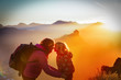 mother and little daughter travel in sunset mountains, family silhouette