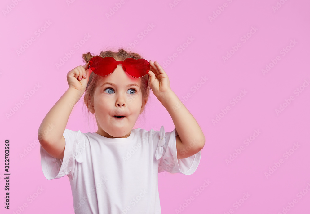 Fototapeta Portrait of surprised cute little toddler girl in the heart shape sunglasses. Child with open mouth having fun isolated over pink background. Looking at camera. Wow funny face