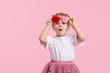 canvas print picture - Portrait of surprised cute little toddler girl in the heart shape sunglasses. Child with open mouth having fun isolated over pink background. Looking at camera. Wow funny face